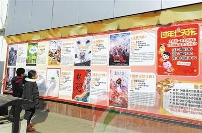 2月2日,市区一家电影院张贴的春节期间上映电影的海报吸引路人驻足